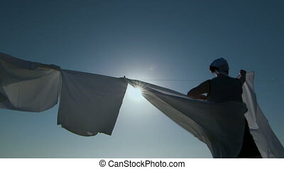 Woman hanging up white laundry on a clothesline against blue...