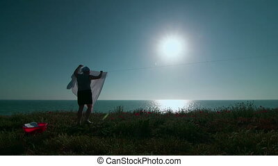 Woman hanging white laundry on her clothes line against blue...