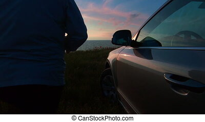 Silhouette of woman near his car at sunset