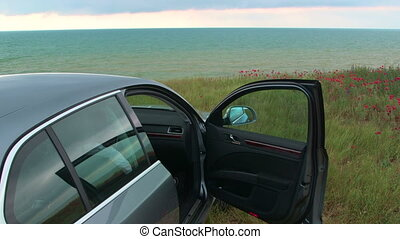 Car is parked with opened door at the seaside in a cloudy...