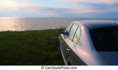 Car parked on the seashore at sunset