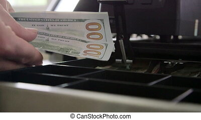 Cashier counts and puts cash into a register