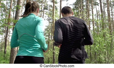 Athletic Couple - Couple jogging in park with their backs to...