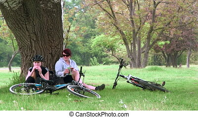 Cyclists resting after cycling in the park - Mother and...