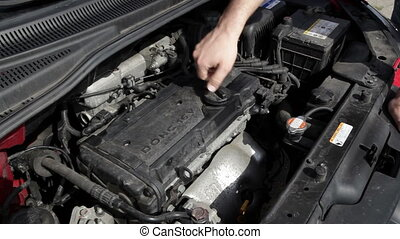Opening the oil cap on the engine block of a compact car