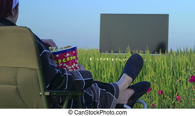Woman watching television in the green field, focus on...
