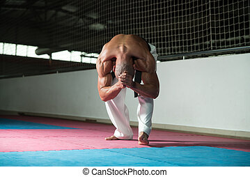 Flexible Man Stretching Before Training - Male Martial Arts...