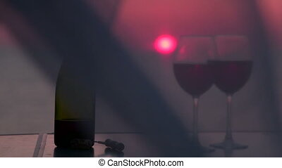 Couple clinking glasses with red wine by the sea at sunset