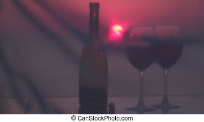 Two glasses of red wine and beautiful sunset by the sea