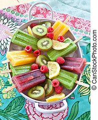 Colorful popsicles with fresh fruits in vintage tray