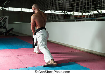 Karate Man In A Kimono Limbering Up - Male Martial Arts...