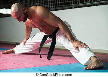 Mature Man Warming Up And Stretching - Male Martial Arts...