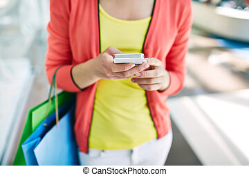 Shopper with cellphone - Female customer with cellular phone...