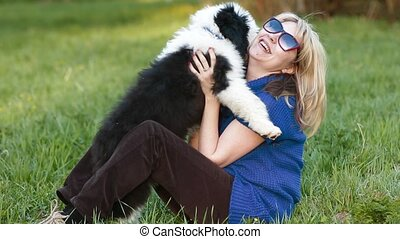 happy blonde with a puppy bobtail - girl hugging a puppy...