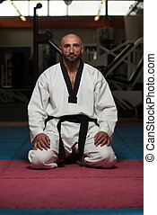 Man In A Kimono With A Black Belt Meditates - Black Belt...