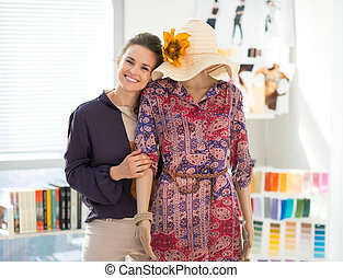 Portrait of happy fashion designer with mannequin