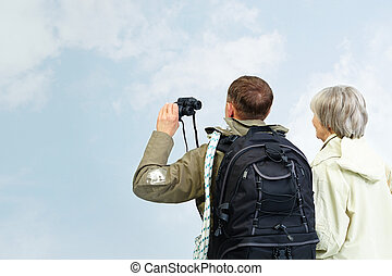 Couple of hikers - Backs of senior hikers with binoculars on...