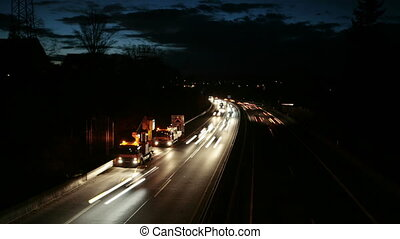 Traffic at dusk - Commuters on highway at dusk. Time lapse