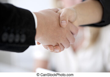 Handshake to seal a deal - with bright office and woman in...