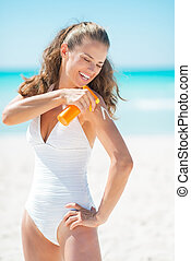 Happy young woman applying sun block creme