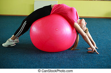 Young woman exercising with fitness ball in gym