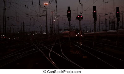 Traffic at the railway station - Arriving train at dusk