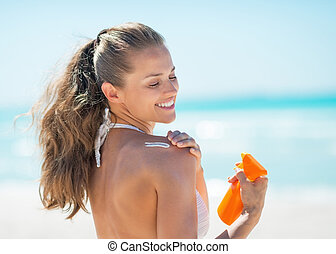 Happy young woman applying sun screen creme