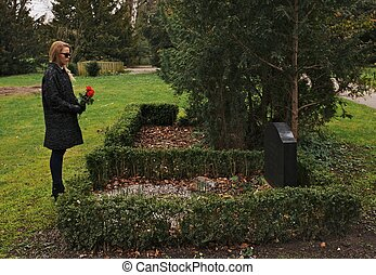 Young woman grieving at cemetery holding flowers - Sad woman...