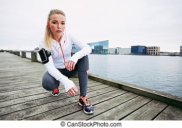Female jogger outdoors looking confident - Young woman...
