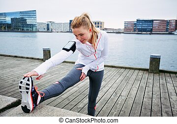 Female runner stretching before a run - Fit young woman...