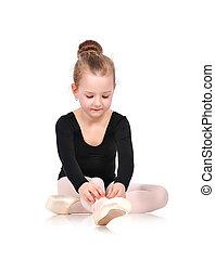 ballerina tying pointe sitting on floor