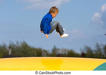 Jumping boy - Boy jumping up and down on bouncy pad....