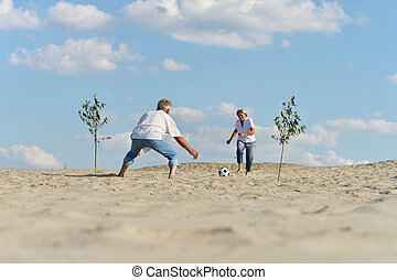 Couple playing football - Mature active couple playng...