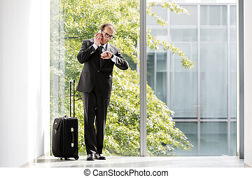 Formal wear Businessman with trolley case looking at his...