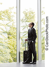 businessman in formal wear holding trolley - businessman in...