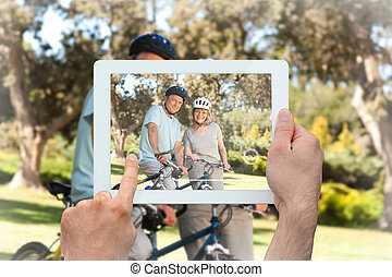 Composite image of hand holding tablet pc - Hand holding...