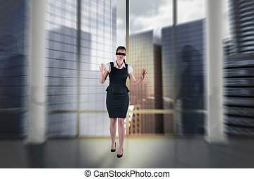 Composite image of redhead businesswoman in a blindfold...