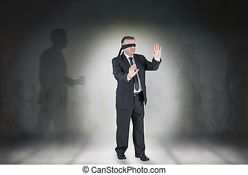 Composite image of mature businessman in a blindfold against...