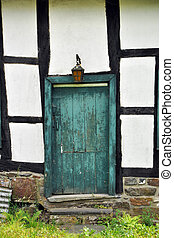 Door - Timber frame facade with a closed crooked old green...