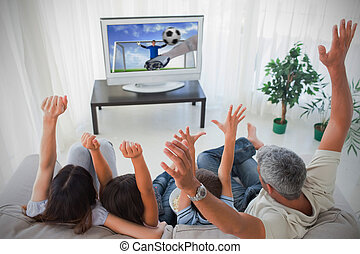 Family cheering and watching the world cup at home in the...