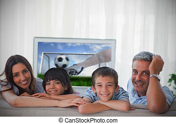 Family smiling at the camera with world cup showing on television