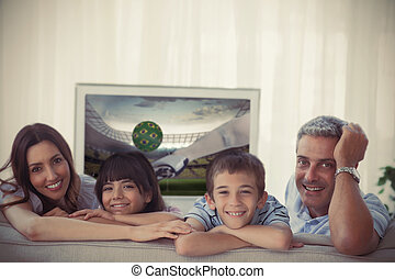 Family smiling at the camera with world cup showing on television at home on sofa