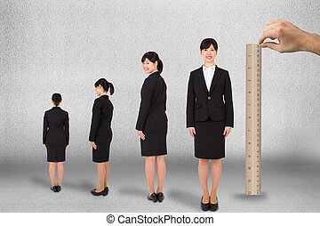 Composite image of hand measuring businesswoman with ruler