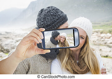 Composite image of hand holding smartphone showing - Hand...