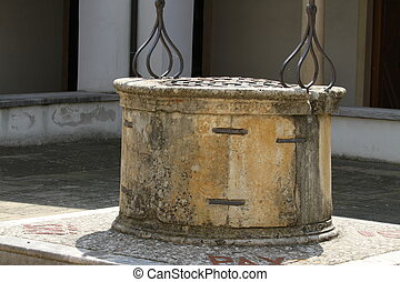 ancient well in marble and stone in a cloister of the...
