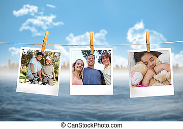 Composite image of instant photos hanging on a line against...