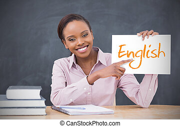 Happy teacher holding page showing english in her classroom...