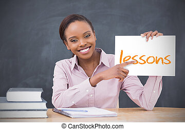 Happy teacher holding page showing lessons in her classroom...