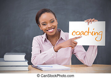 Happy teacher holding page showing coaching in her classroom...