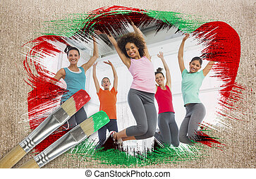 Composite image of fitness class at the gym with paintbrush...